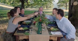Happy group of people around a table enjoying food outdoors along with cannabis